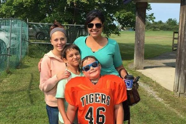 Photo of Emily and her kids at a football game